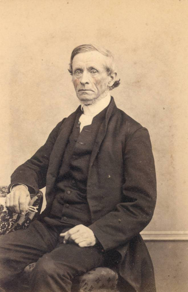 19th century quaker man sitting holding glasses