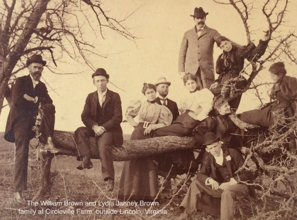 old photograph of family on fallen tree